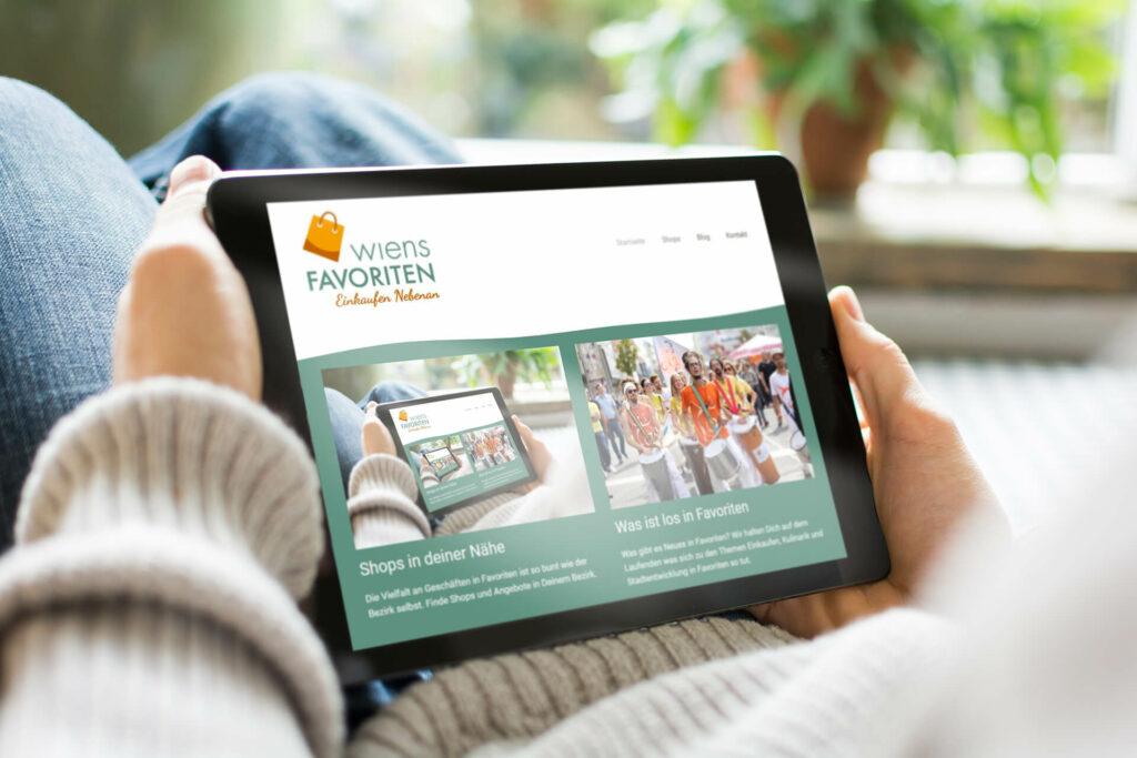 Tablet mit der Website von Wiens Favoriten am Schoß.
