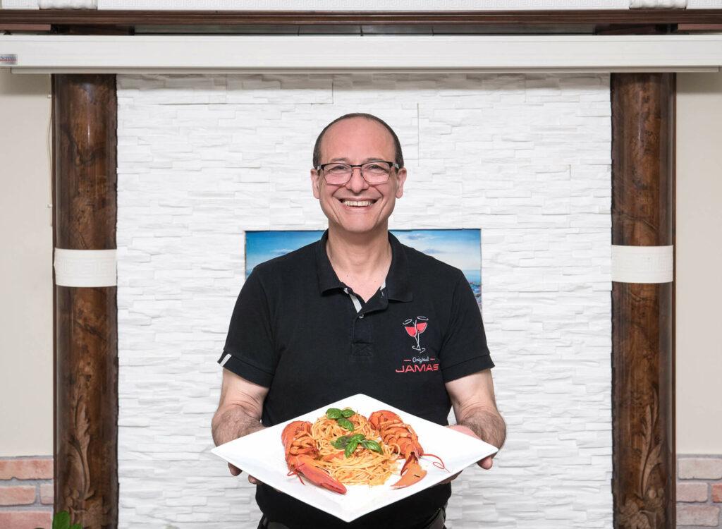 Der Besitzer des griechischen Restaurants Jamas präsentiert lächelnd ein griechisches Nudelgericht mit Meerestieren.